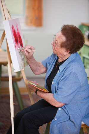 activity: Old woman paints a picture Stock Photo