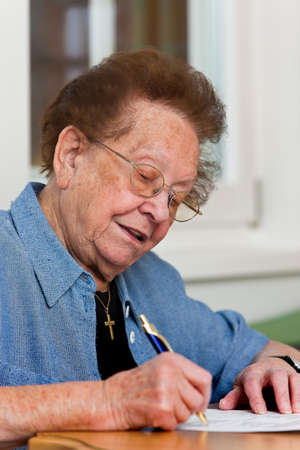 Old woman writes a letter photo