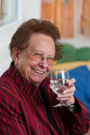 Old woman drinking water from a glass Stock Photo