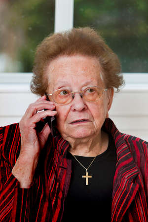 Old woman carries a telephone conversation with mobile phone photo