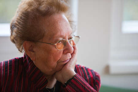 inhibited: An old woman sits thoughtfully at the window Stock Photo