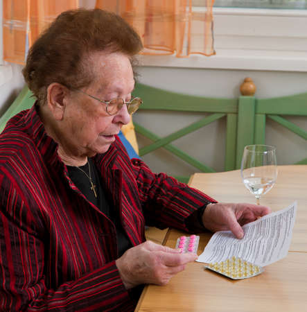 leaflet: Old Woman with tablets and leaflet Stock Photo