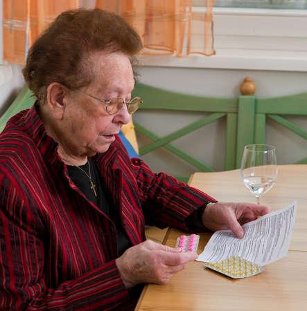 bijsluiter: Oude vrouw met tabletten en bijsluiter