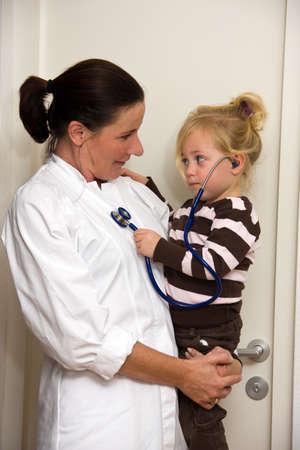Pediatrician investigates a child in surgery photo