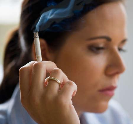 joven fumando: Una mujer con fumar un cigarrillo Foto de archivo