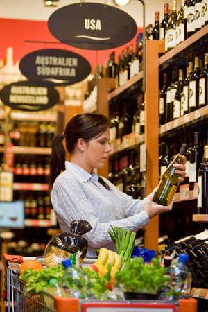 Junge Frau in einem Supermarkt zu kaufen Wein Lizenzfreie Bilder