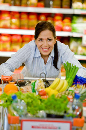 retailing: Young woman in the supermarket to buy food and a fruit Stock Photo