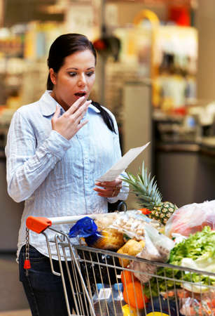controls: Young woman controls a bill of sale in supermarkets