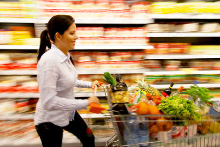Young woman with shopping cart in the supermarket when shopping Stock Photo