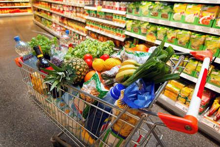 super human: Completo inkaufswagen con frutas vegetales alimentos en el supermercado