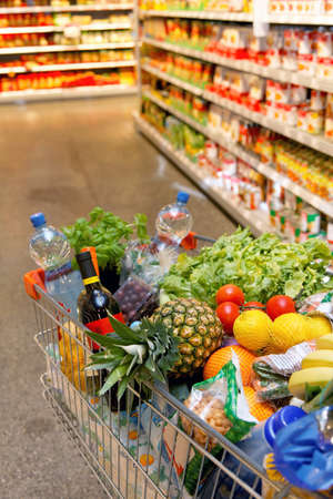 business products: Full inkaufswagen with fruit vegetable food in supermarket Stock Photo