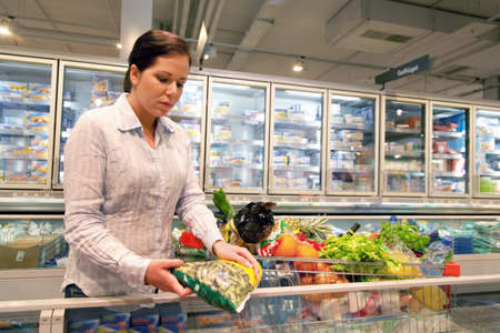 refrigerated: Young woman in the supermarket to buy food and fruit one. Stock Photo