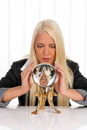 Young woman interprets the future from a crystal ball in their hands photo