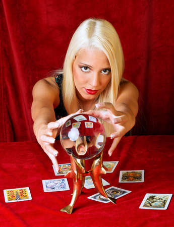summoning: Young woman interprets the future from a crystal ball in their hands