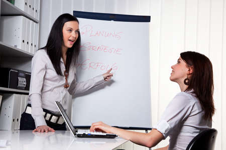 Young women in a business coaching model explains success Stock Photo
