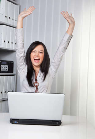 Young woman raises her arms jubilantly on the computer
