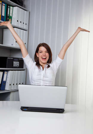 Young woman raises her arms jubilantly on the computer Stock Photo - 4476575