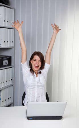 Junge Frau wirft die Arme jubelnd auf dem Computer