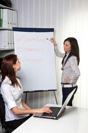 Young women in a business coaching model explains success photo