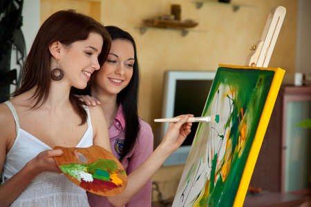 paintings on canvas: Young woman paints in her spare time with oil paints on a easel