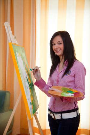 oil paints: Joven pinta en su tiempo libre con la pintura al �leo sobre un caballete