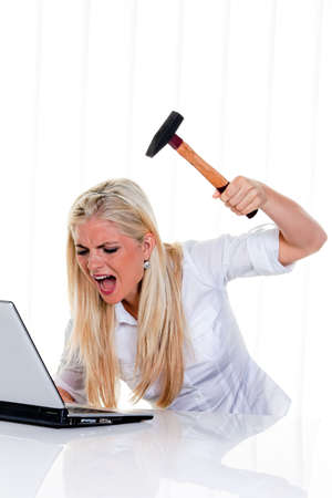 Furious businesswoman with hammer, yelling and preparing to smash her laptop. Vertical. photo