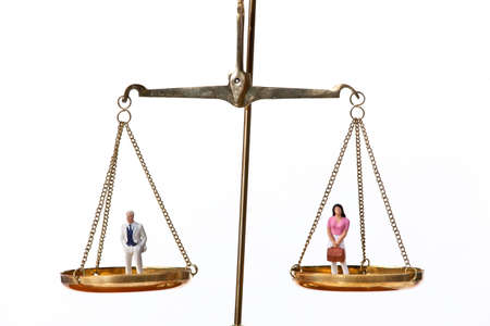 human gender: Set of scales, with businessman figure on one side and businesswoman figure on the other. Horizontal.