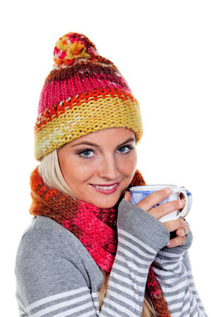Young woman in winter clothing drinking from a mug. Vertically framed shot. photo