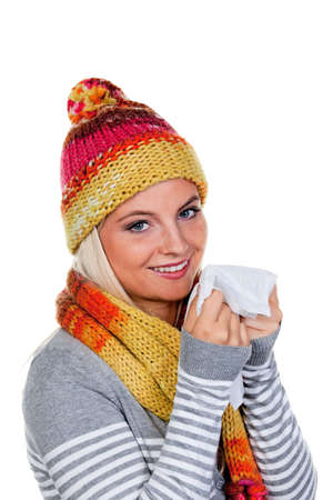 Young woman in winter clothing and holding tissue. Vertically framed shot. photo