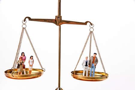 unbalanced: Dolls on balancing scales. Horizontally framed shot.