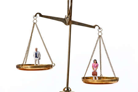 gender equality: Dolls on balancing scales. Horizontally framed shot.
