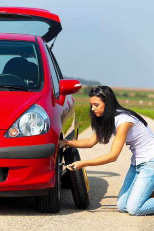 Young woman changing tire by the side of a rural road. Vertical. Stock Photo - 5945350