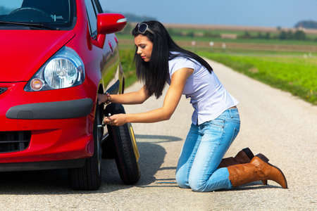 fixing: Young woman crouched down and changing a tire on her car. Horizontally framed shot. Stock Photo