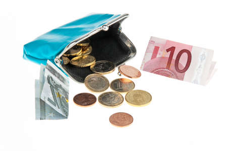 coin purse: Paper currency and coins coming out of open coin purse. Horizontally framed shot. Stock Photo