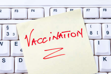 h1n1 vaccinations: Close-up of adhesive note with vaccination reminder on computer keyboard. Horizontally framed shot.