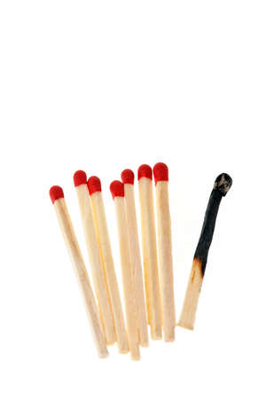 burned out: Row of matches with one burnt matchstick. Vertically framed shot. Stock Photo
