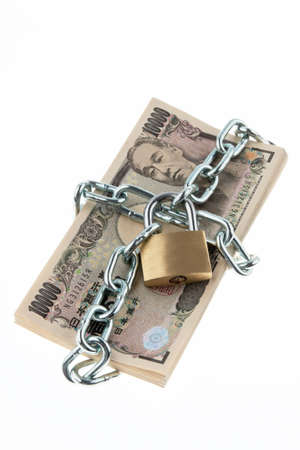 unreachable: Japanese currency with chain and lock. Vertically framed shot.