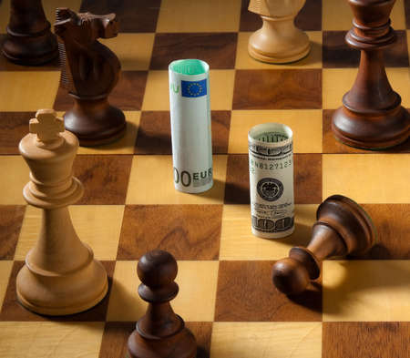 Euro and Dollar on a chessboard. Square format. photo