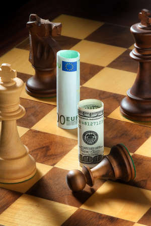 monetary policy: Euro and dollar on a chessboard. Vertically framed shot. Stock Photo