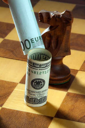 Euro tipping over dollar on chessboard. Vertically framed shot. photo