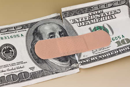 health risk: Many dollars banknotes with a plaster. Liabilities in the policy