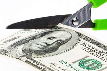 rescheduling: U.S. dollars bills and scissors. Duties and taxes. Stock Photo