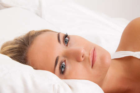doze: A young woman lies awake in bed. Sleepless and thoughtful.