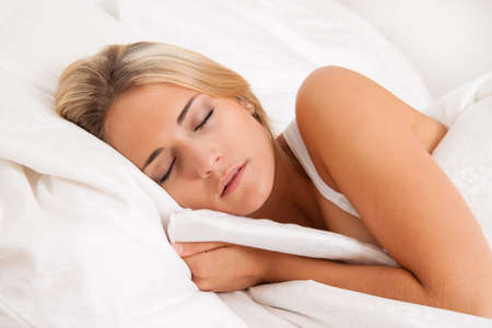 A pretty young woman sleeping in bed recovering. Stock Photo - 7808391