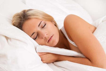 cansancio: Una mujer bastante joven, durmiendo en la recuperaci�n de la cama.  Foto de archivo