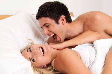 Couple has fun in bed. Laughter, joy and eroticism in the bedroom Stock Photo - 7808383