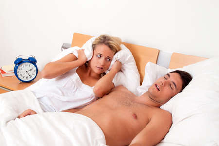 snoring: Pair in Scvhlafzimmer. Husband snores loud and unpleasant. Stock Photo