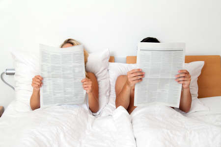 A young couple in bed reading a newspaper. Information and news photo