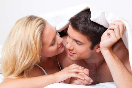 relaciones sexuales: Pareja tiene diversión en la cama. Risa, la alegría y el erotismo en el dormitorio
