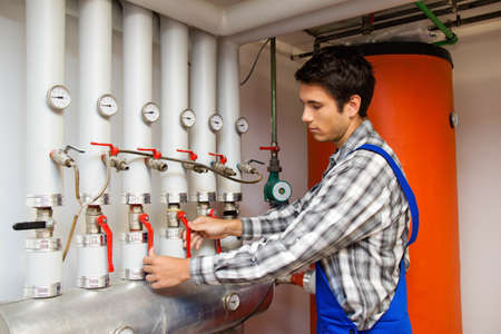 to heat: Young heating engineer in a boiler room for heating system